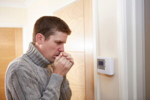 cold-man-checking-thermostat